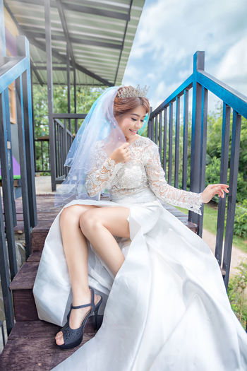 Full Length Of Bride Sitting On Staircase By Railing