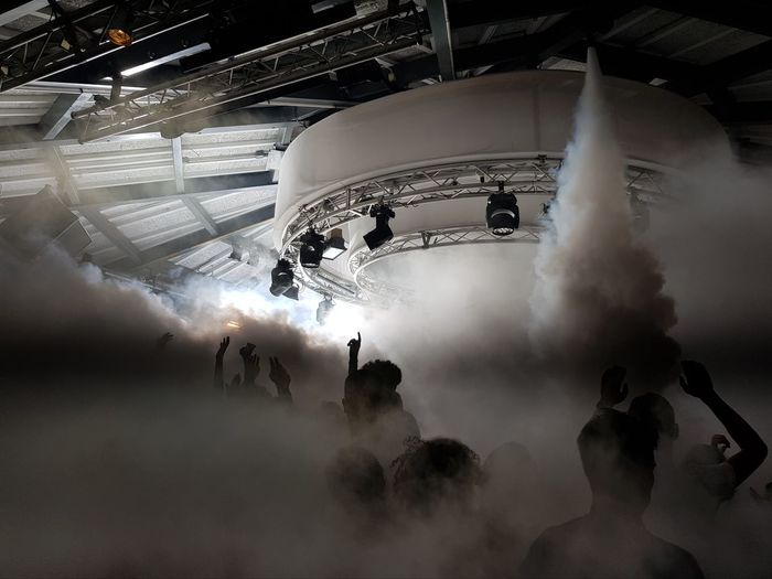 People dancing on stage amidst smoke