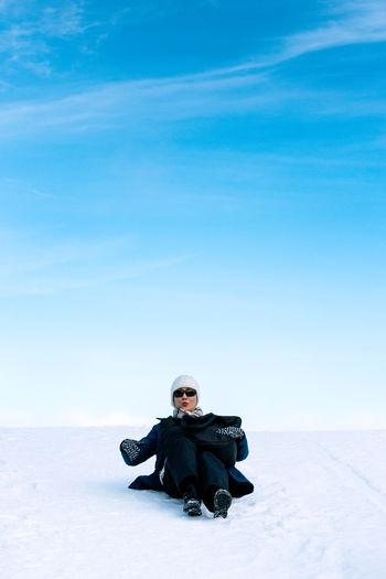 Full Length Of Woman Sliding On Snow Covered Slope Against Blue Sky