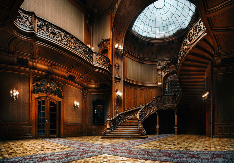 Lviv, Ukraine. House of Scientists. Interior of the magnificent mansion with ornate grand wooden staircase in the great hall. A former national casino. Architecture Built Structure Indoors  Building Arch Illuminated The Past Lighting Equipment Staircase No People Luxury Ornate Design Wooden Curved  Mansion