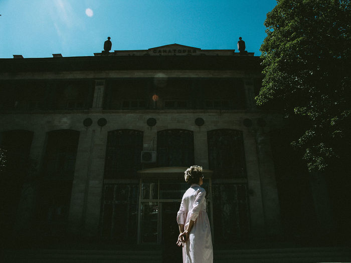Low angle view of woman standing by statue against building