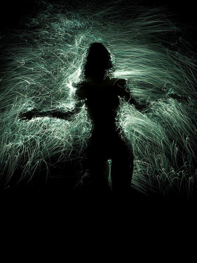 Silhouette woman with arms outstretched standing at night