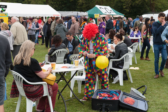 Clown putting sugar in coffee at open air free music festival [Larks in the parks] in Liverpool. Adult Checked Coat Checked Pattern Clown Coffee Colourful Crowd Day Family Event Field Large Group Of People Lawn Furniture Open Suitcase Outdoors People Sitting People Walking  Plastic Furniture Red Wig Sitting Suitcase Summer Tents Women Yellow Balloon Youth Culture