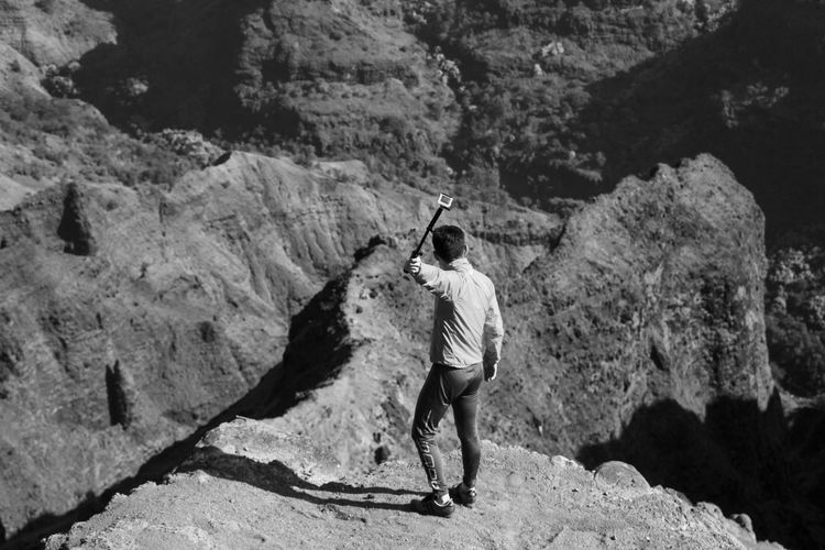 Rear view of man standing on rock