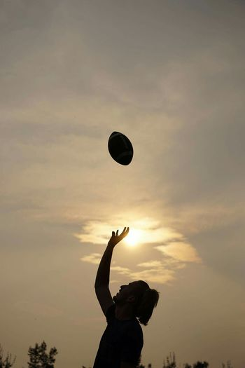 Silhouette Woman Playing Rugby Against Sky During Sunset