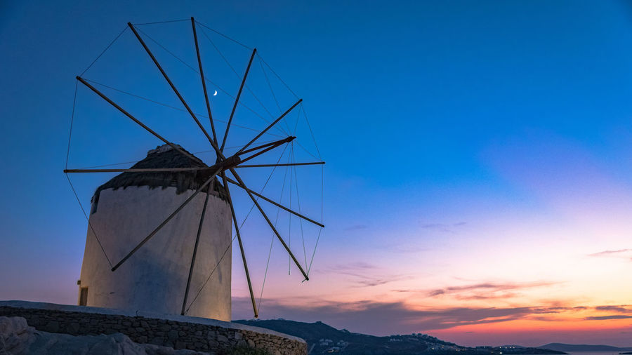 Low angle view of traditional windmill against sky at sunset