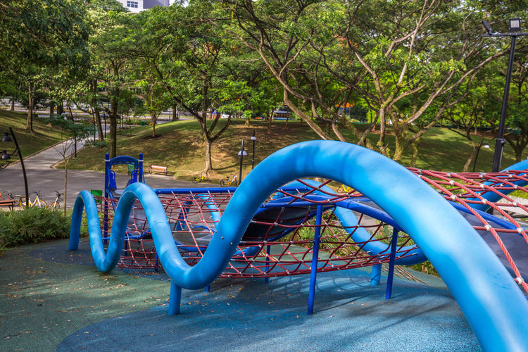 Playground - Admiralty Park. Modern loops, twirls and slides Absence Architecture Blue Childhood Day Empty Fun Growth Jungle Gym Merry-go-round Metal Nature Outdoor Play Equipment Outdoors Park Park - Man Made Space Plant Playground Slide Slide - Play Equipment Tree