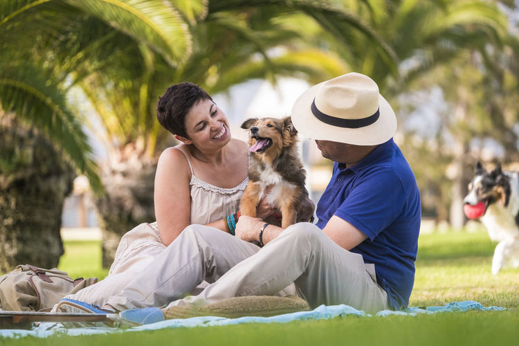Couple sitting with dog at park