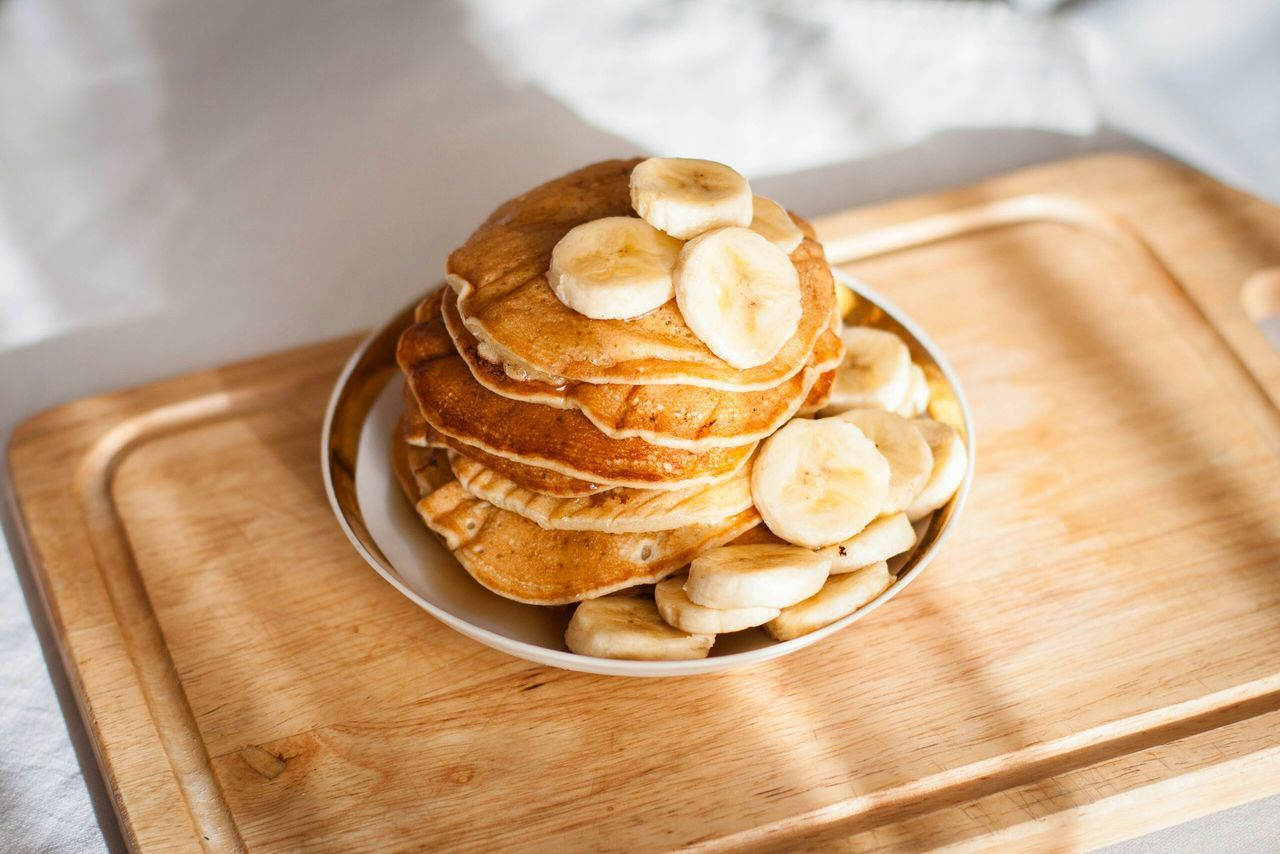 High angle view of pancakes with banana in plate on table
