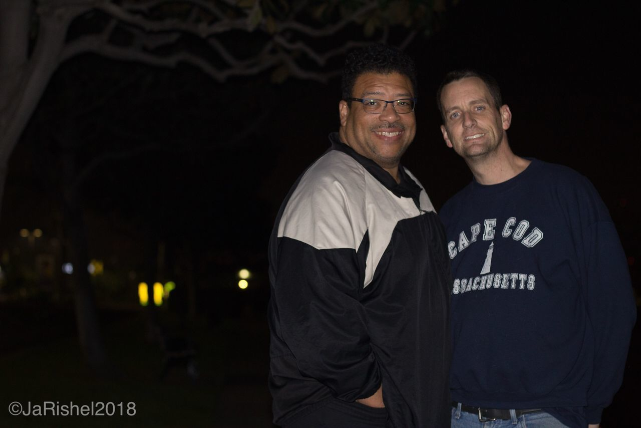 looking at camera, portrait, night, waist up, smiling, two people, confidence, togetherness, standing, outdoors