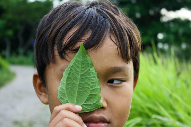 Close-up portrait of boy holding leaf