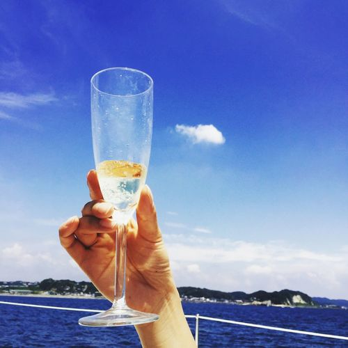 Cropped Image Of Hand Holding Champagne Flute Against Blue Sky