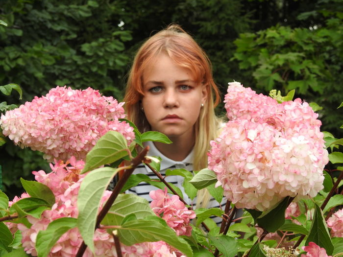 Portrait of girl by pink flowering plants