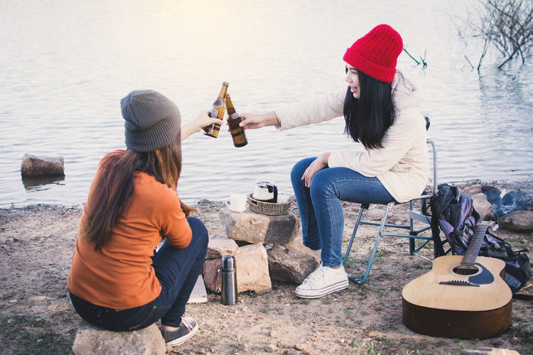 Friends Toasting Beer At Lakeshore During Picnic