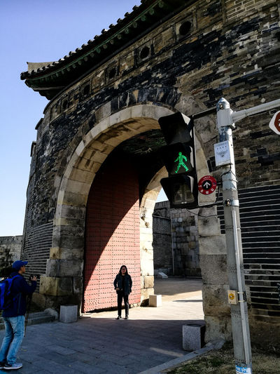 Trio Entrance Gate Fortress Gate Tourists Holiday Destination Traffic Light  Green Man City Men Shadow Standing Arch Silhouette Architecture Sky Building Exterior Built Structure Archway Historic Building Historic Entryway History Castle Visiting Fort Civilization Fortress Fortified Wall Stone Wall Medieval Focus On Shadow