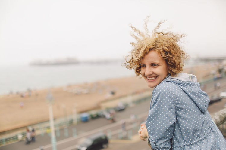Beach Blonde Brighton Brighton Pier Casual Clothing Curly Hair Cute Day Focus On Foreground Girl Hair In The Wind Leisure Activity Lifestyles Nature Outdoors Portrait Seaside Shore Sky Smile Smiling Summer Warm Clothing People And Places Connected By Travel Moments Of Happiness