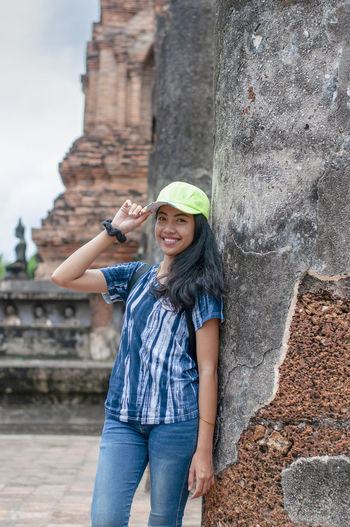Portrait of happy young woman standing against built structure