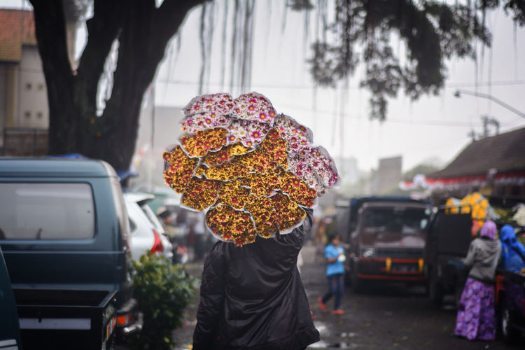 Man with umbrella on street during rainy season