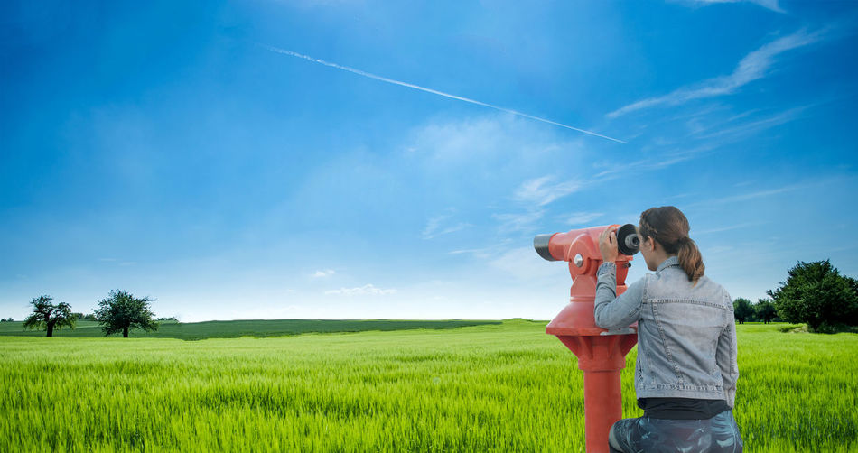 Young woman looking through tourist telescope, exploring landscape. Plant Field Sky Land Environment Standing Three Quarter Length Holding Women Nature Adult Grass Cloud - Sky Landscape Day Beauty In Nature Females Child Two People Side View Mature Adult Outdoors