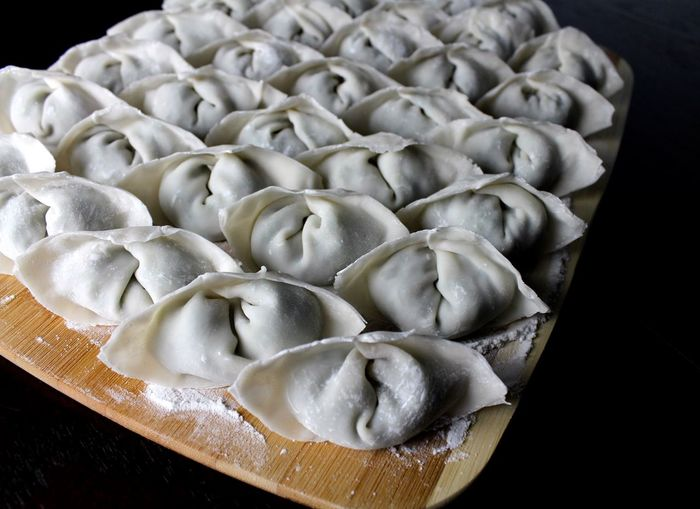 High angle view of dumplings on cutting board over black background