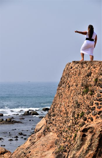 Rear View Of Woman Standing On Cliff By Sea Against Clear Sky