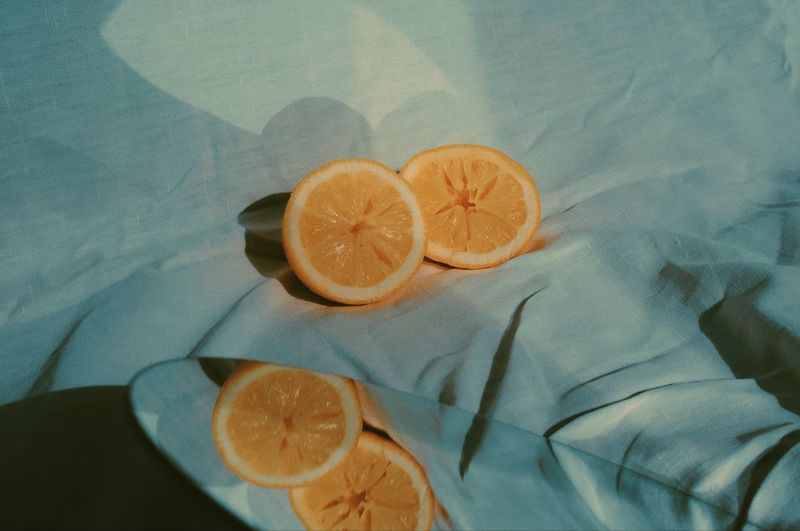 High angle view of orange slice on textile