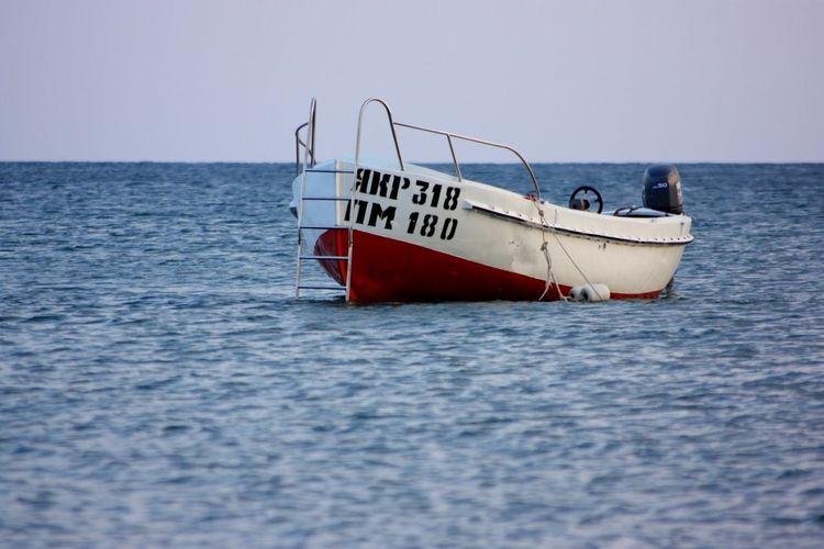 Motorboat moored in sea against clear sky