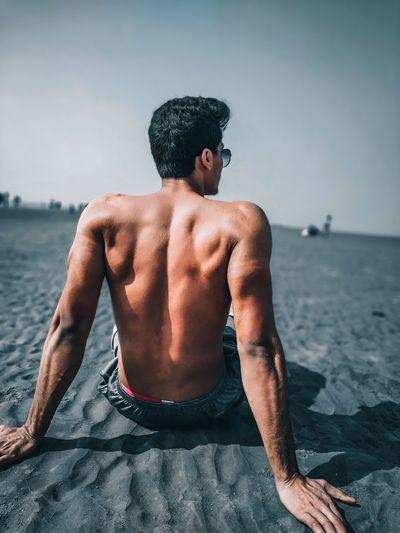 Rear view of shirtless man sitting on sea shore