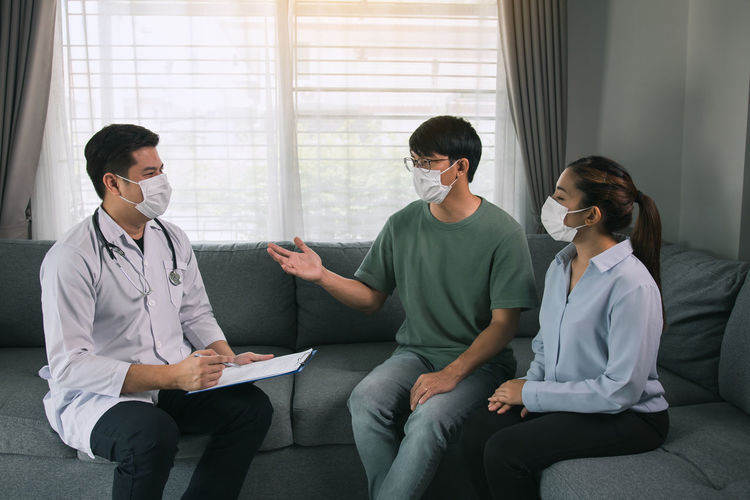 Young couple wearing mask having discussion with doctor at home