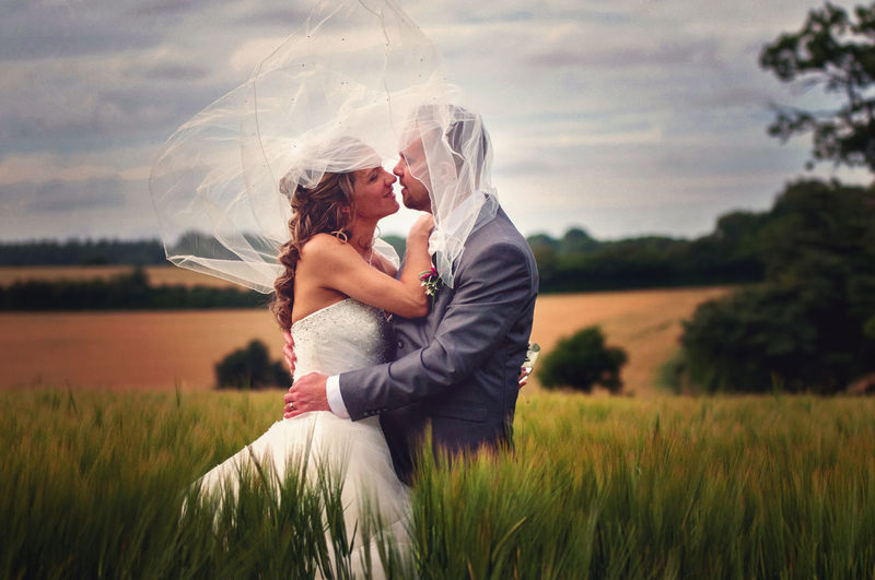 Bride and groom embracing while standing on grassy field