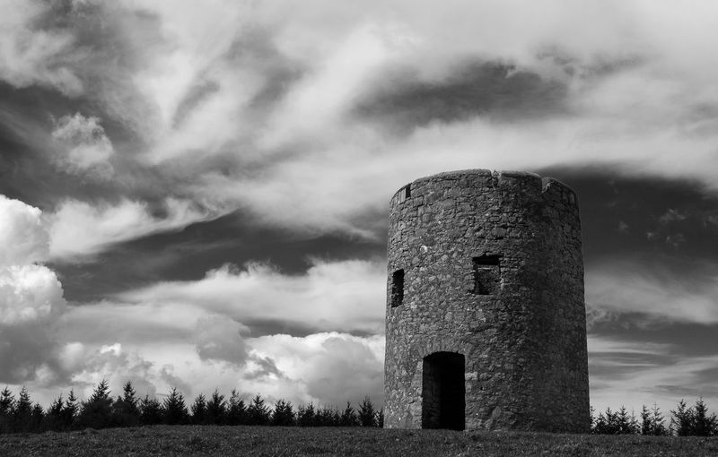 Low angle view of castle on land against cloudy sky