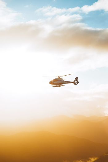 In the light. Air Vehicle Mode Of Transportation Sky Flying Transportation Cloud - Sky Mid-air on the move Low Angle View Outdoors Airplane No People Day Nature Sunset Travel Helicopter Beauty In Nature Orange Color Motion