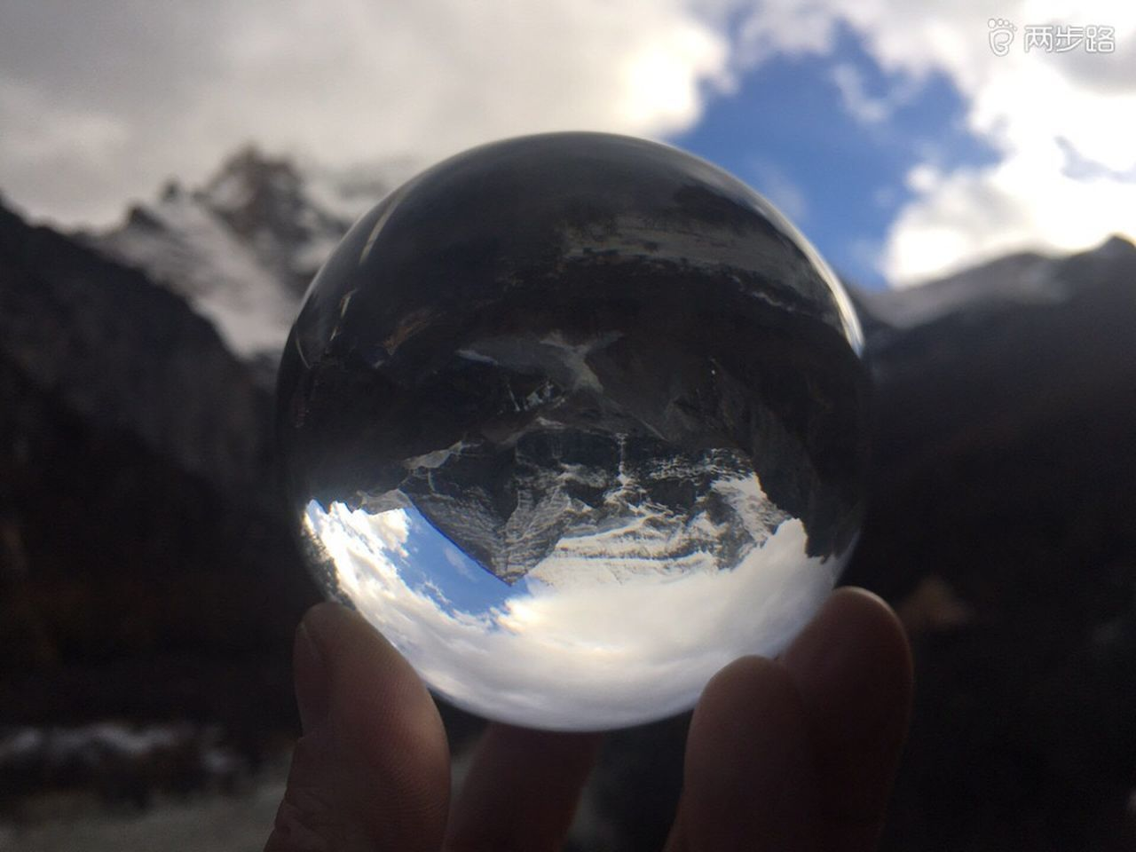 human hand, holding, hand, human body part, one person, sphere, nature, crystal ball, unrecognizable person, human finger, close-up, sky, finger, focus on foreground, body part, transparent, real people, ball, reflection, outdoors