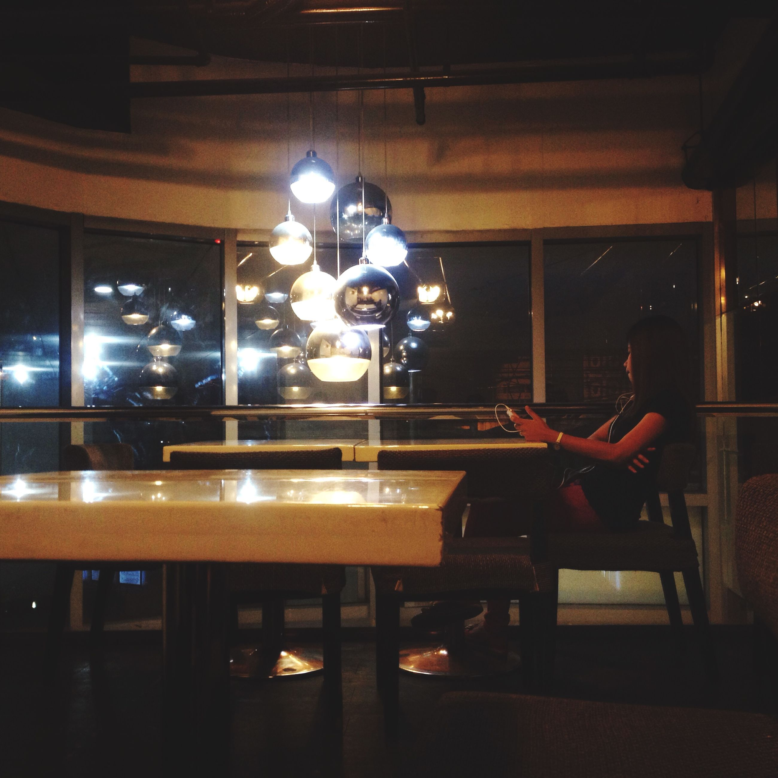 indoors, illuminated, lighting equipment, night, table, glass - material, window, electric lamp, reflection, electric light, built structure, home interior, restaurant, architecture, electricity, light bulb, transparent, hanging, luxury, dark