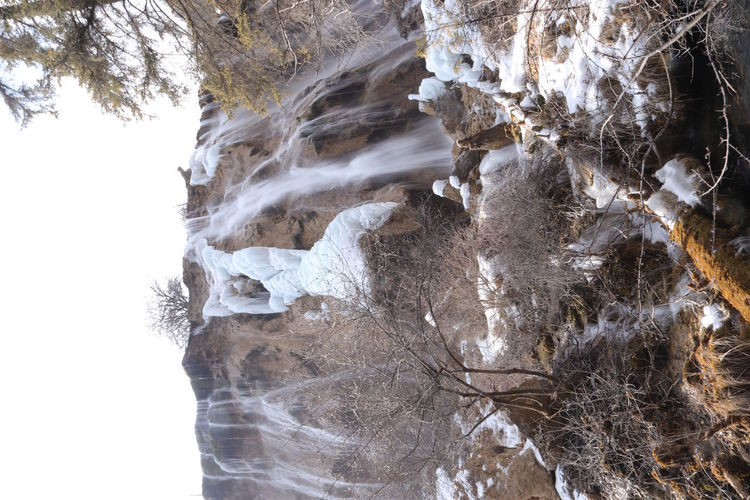 Icicles on rock against sky during winter