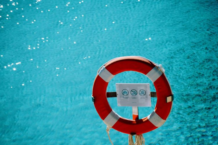 Close-up of rescue ring on swimming pool against sea