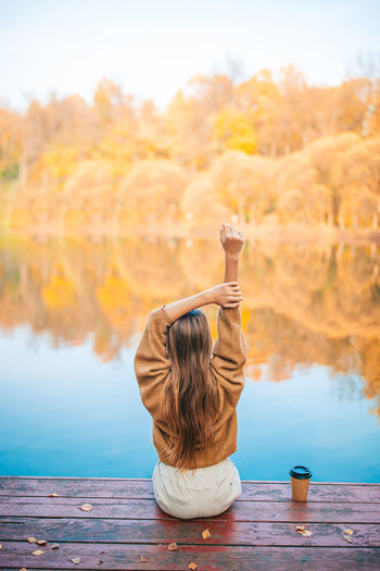 Rear view of woman sitting by lake during autumn