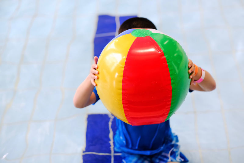 Rear view of a boy holding toy in swimming pool