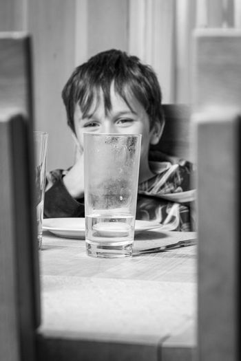 Portrait of boy drinking glass on table
