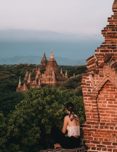 Woman sitting and watching the sunrise over the temples of Bagan, Myanmar Ancient Sitting Temples Travel View Views Woman Bagan Bagan, Myanmar Burma Looking At View Myanmar No Face One Woman Only Outdoor Sky Temple Temple Landscape Travel Destinations View Into Land