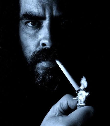 Close-Up Portrait Of Man Lighting Cigarette Against Black Background