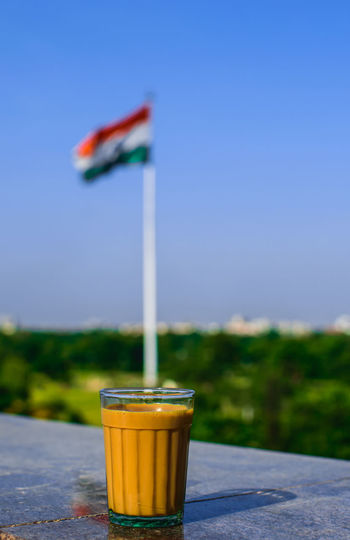 Tea in glass on retaining wall against indian flag