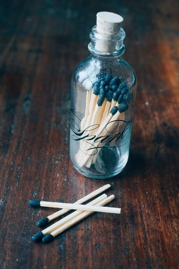 Close-up of matchsticks in glass bottle on wooden table