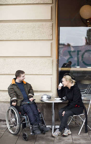 Man and woman sitting in front of cafe