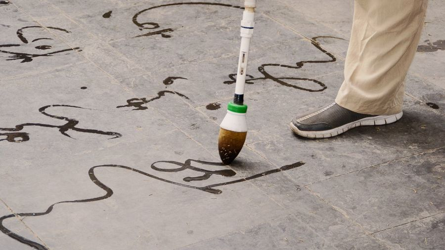 Low section of man practicing calligraphy with water brush on street