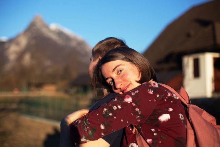 Portrait of smiling woman embracing boyfriend