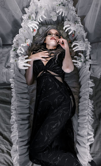 Portrait of young woman lying down on bed