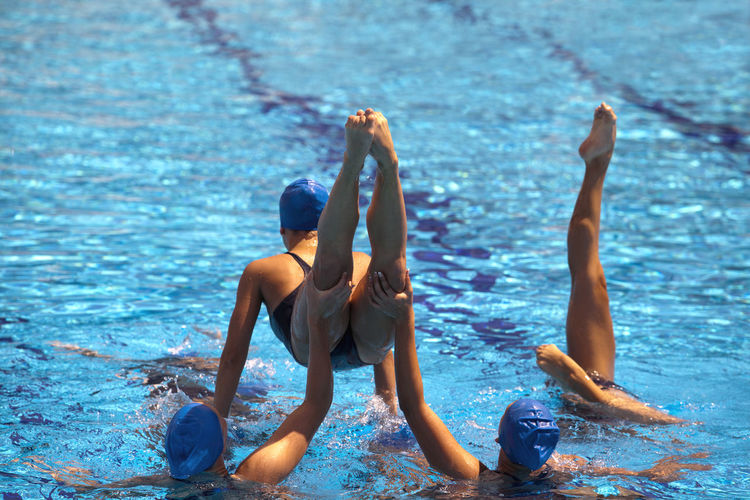 Swimmers doing gymnastics in pool