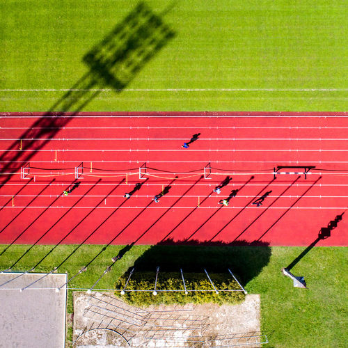 Sport Grass Running Track Track And Field Competition Outdoors Stadium Competitive Sport High Angle View Playing Field Sunlight Motion Shadow Above Jogging Running Marathon Summer Aerial View From Above  Aerial Action People