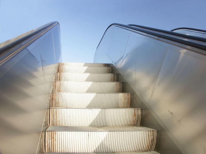 Closeup of exterior escalator viewed upwards with clear blue sky in the background